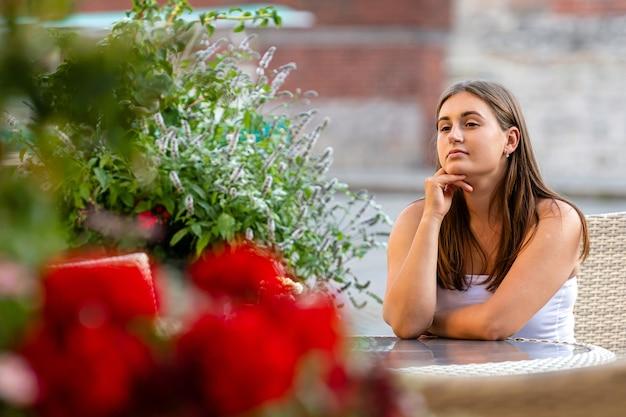ストリートカフェのテーブルに座って、会議を待っている若い美しい女性、フォアグラウンドで多重花