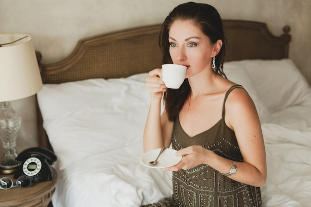 Young beautiful woman sitting on bed in hotel, stylish dress, sensual mood, drinking coffee, holding cup
