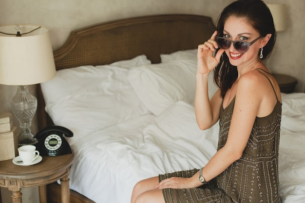 Young beautiful woman sitting on bed in hotel, stylish dress, smiling, happy, sunglasses