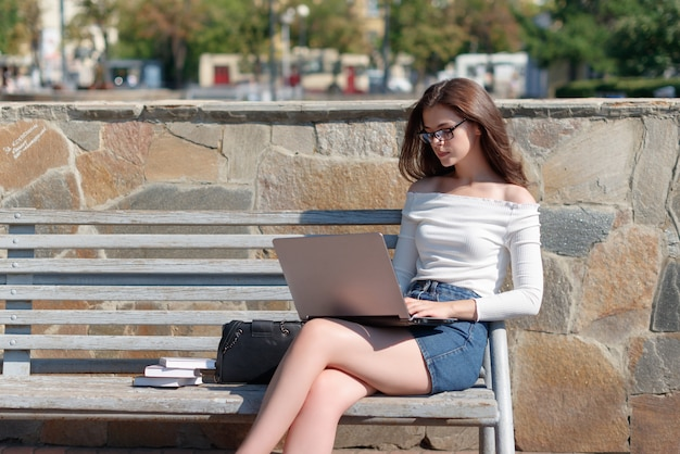 Young beautiful woman sitting on a bench in the park and working on a laptop