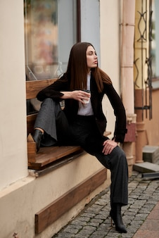 Young beautiful woman sitting on a bench with and drinking coffee