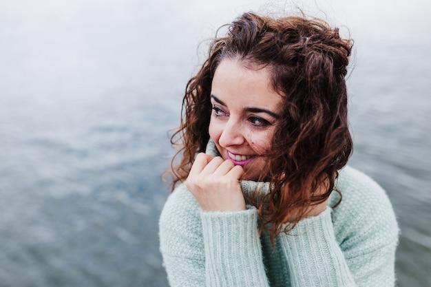 Молодая красивая женщина, сидя у реки на закате, наслаждаясь видами порту. концепция путешествия