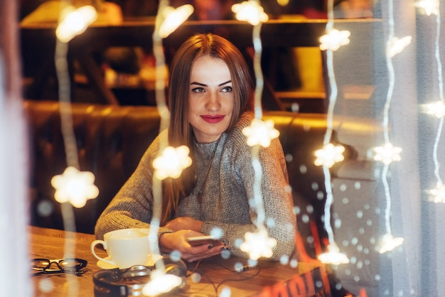 Young beautiful woman sitting in cafe, drinking coffee. christmas, new year, valentines day, winter holidays