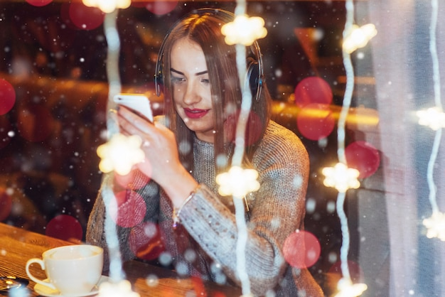Young beautiful woman sitting in cafe, drinking coffee. model listening to music. christmas, happy new year, valentines day, winter holidays
