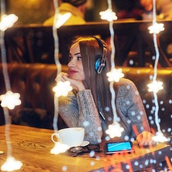 Young beautiful woman sitting in cafe, drinking coffee. model listening to music. christmas, new year, valentines day, winter holidays