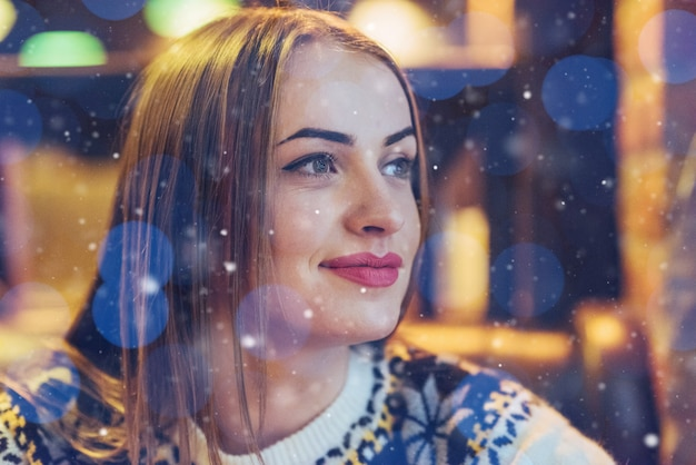 Young beautiful woman sitting in cafe, drinking coffee. model looking up. christmas, new year, valentines day, winter holidays