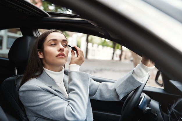 Young beautiful woman sitting in car, driving on meeting and applying mascara, looking at rear-view mirror
