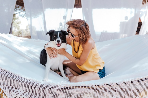 Young beautiful woman sitting on hammock with her border collie dog outdoors