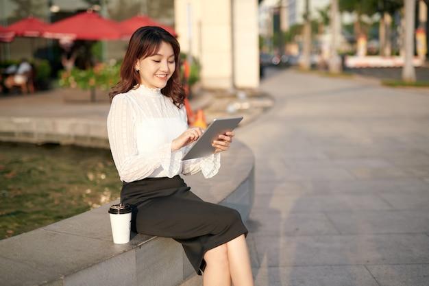 Молодая красивая женщина, сидя в центре города в солнечный день, с помощью цифрового планшета возле бара кафе, улыбаясь.