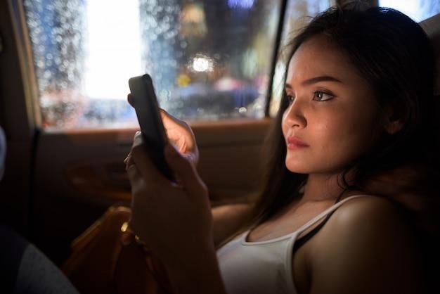 Молодая красивая женщина, сидя в машине такси, используя мобильный телефон ночью