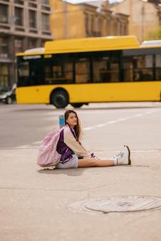 보도 한가운데에 앉아 있는 아름다운 젊은 여성