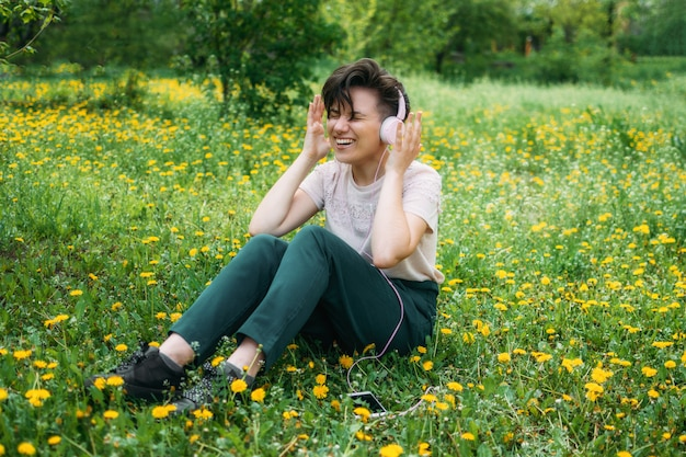 Young beautiful woman sitting on the lawn green grass with dandelions and listening to music