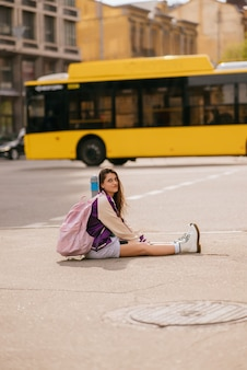 Young beautiful woman sitting in the middle of the sidewalk