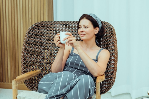 Young beautiful woman sitting in a modern armchair girl drinking coffee and reading a magazine in the hotel lobby