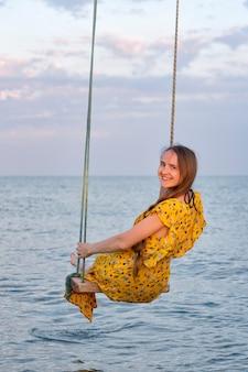 Молодая красивая женщина, сидя на качелях веревки на фоне моря.