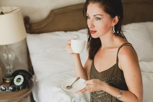 Молодая красивая женщина сидит на кровати в отеле, стильное платье, чувственное настроение, пьет кофе, держит чашку