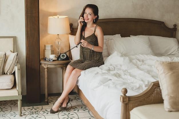 ホテルのベッドに座っている若い美しい女性、スタイリッシュなイブニングドレス、官能的な気分、電話で話す、笑顔、軽薄、探している、セクシー
