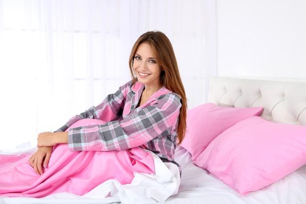 ベッドに座っている若い美しい女性