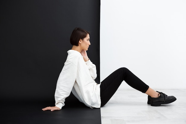 검은 색과 흰색 표면 위에 바닥에 앉아 젊은 아름 다운 여자