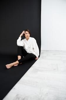 黒と白の表面の上の床に座っている若い美しい女性