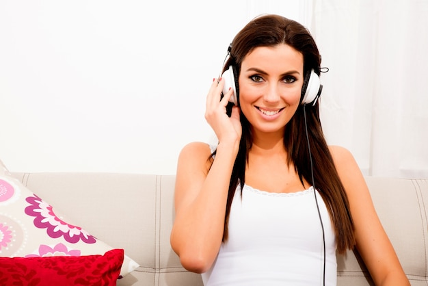 Молодая красивая женщина сидит на диване и слушает аудио в наушниках