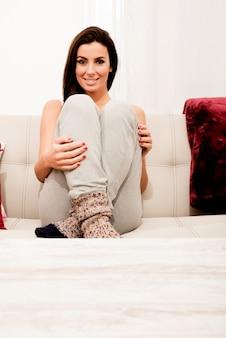 Молодая красивая женщина, сидя на диване