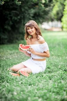 잔디에 앉아 젊은 아름 다운 여자와 수 박을 먹는다. 잔디에 휴식하는 행복 한 소녀. 따뜻한 여름. 수박.