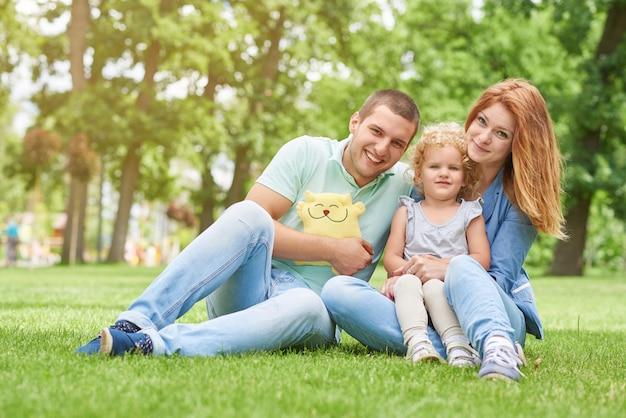 幸せな夫と愛らしい小さな娘のcopyspaceと草の上に座っている若い美しい女性は、家族の結婚生活の季節の楽しみリラックスレクリエーションのコンセプトが大好きです。