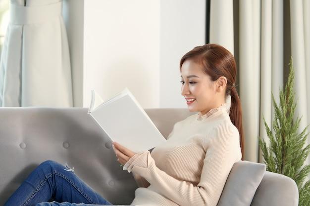 Молодая красивая женщина сидит на диване и читает книгу, наслаждаясь чаем в гостиной дома