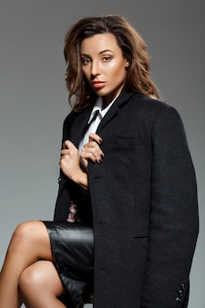 Молодая красивая женщина сидит над серой стеной