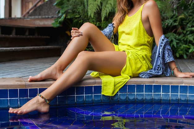 Young beautiful woman sitting at pool in yellow boho dress, summer trend fashion, sexy, skinny, tanned skin, slim legs, tropical vacation, resort hotel, details