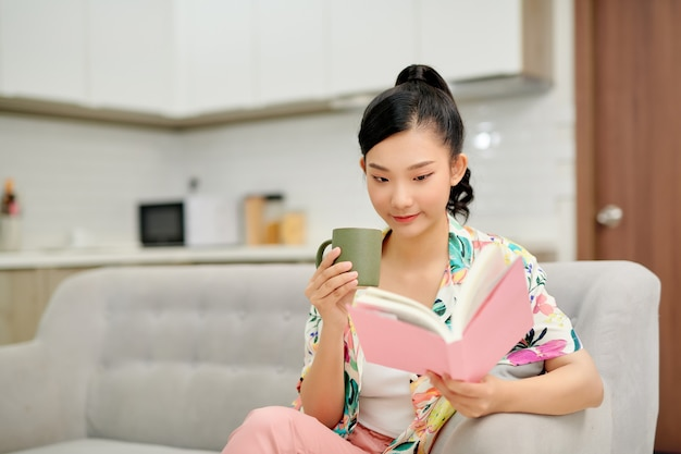 Young beautiful woman sitting on the sofa reading a book enjoying her tea in living room at home