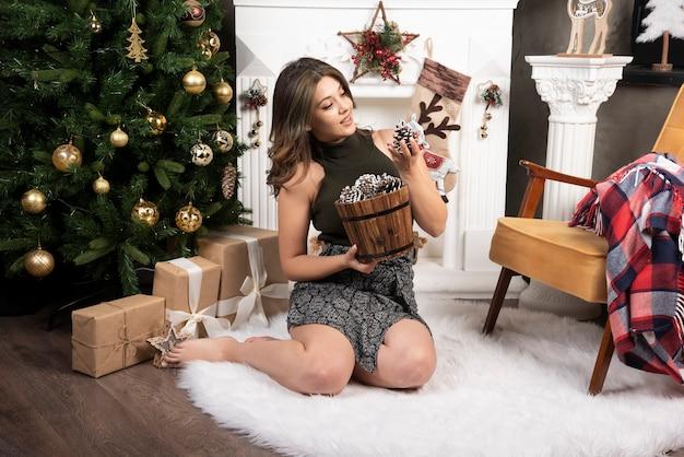 Giovane bella donna seduta con cesto di pigne vicino all'albero di natale