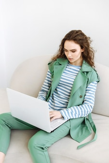 인터넷을 사용하여 노트북과 함께 앉아 젊은 아름 다운 여자
