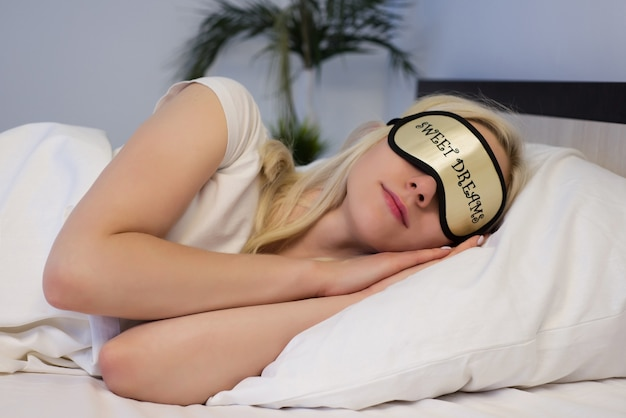 Young beautiful woman sleeping in bed with eye mask - image