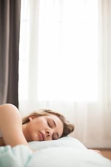 彼女のベッドで寝て、朝リラックスしている若い美しい女性。