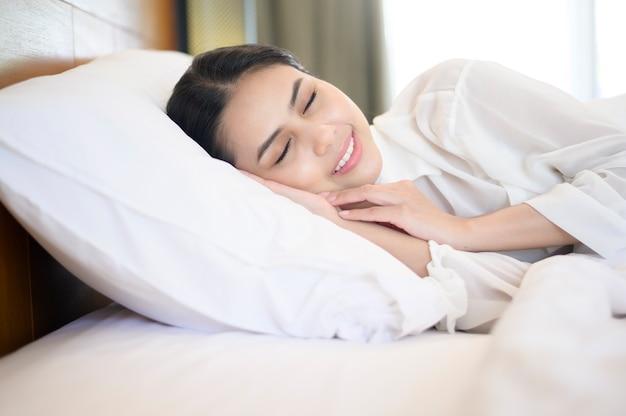 自宅のベッドで寝ている若い美女。