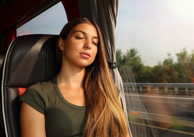 バスに座って寝ている若い美しい女性。バスの乗客が座席に座って寝ている。