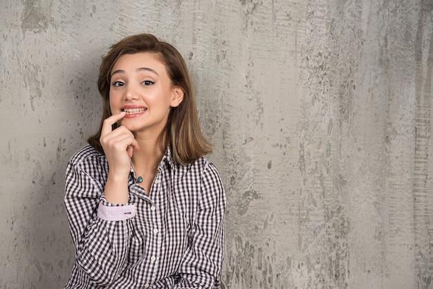자신감이 보여주는 웃 고 손가락 이빨과 입으로 가리키는 젊은 아름 다운 여자