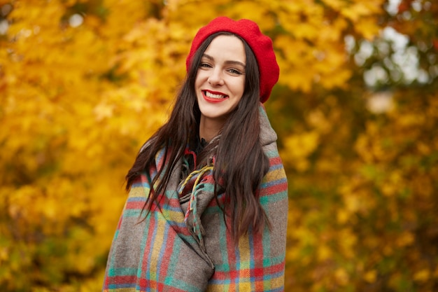 Young beautiful woman smiling female, wearing fashionable red beret and wrapped checkered blanket posing