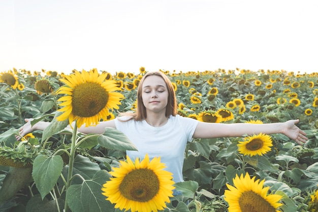 Young beautiful woman smiling and having fun in a sunflower field on a beautiful summer day with open arms.