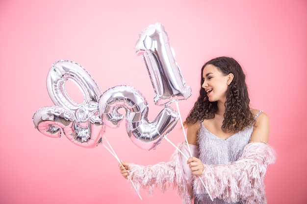 Молодая красивая женщина улыбается на розовой стене с серебряными воздушными шарами для новогодней концепции