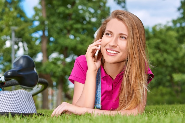 地元の公園の通信チャットキャリアモビリティライフスタイル休日リラクゼーションコンセプトで草の上に横たわる彼女のスマートフォンで話して笑っている若い美しい女性。