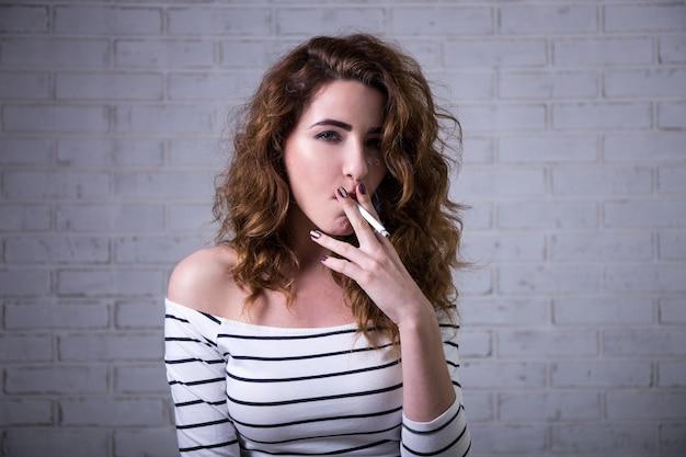 Молодая красивая женщина курит сигарету над белой кирпичной стеной