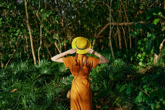 Young beautiful woman spacetropics jungle with hat walks spacepark, naturalist