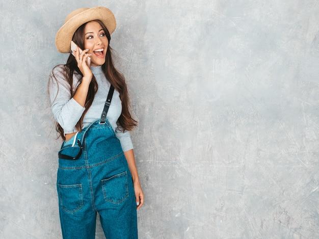 電話で話す若い美しい女性。カジュアルな夏のオーバーオールの服と帽子でトレンディな女の子。