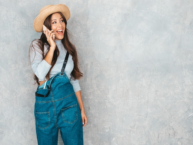 Young beautiful woman speaking on phone. trendy girl in casual summer overalls clothes and hat.