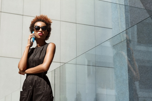 Young beautiful woman speaking on phone walking down city