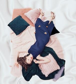 白い絹のようなシーツでキングサイズのベッドで週末を過ごす若い美しい女性。トップダウンビュー。