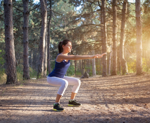 Young beautiful woman sports in the autumn forest at sunset